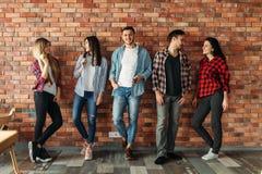 站立在砖墙的小组学生 库存图片