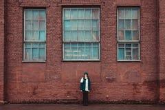 站立在砖墙附近的女孩 库存照片