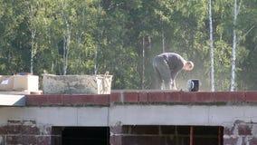 站立在砖金属楼房建筑的一个年轻人削减了电工具研磨机金属结构 影视素材