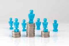 站立在硬币堆顶部的男性和女性小雕象 免版税库存照片