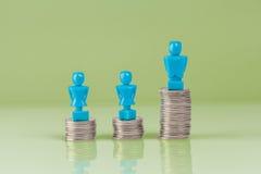 站立在硬币顶部的男性和女性小雕象 库存图片