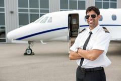 站立在私人喷气式飞机前面的微笑的飞行员 免版税库存图片
