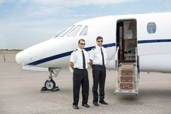 站立在私人喷气式飞机前面的飞行员 库存图片