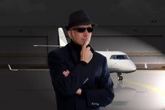 站立在私人喷气式飞机旁边的商人 免版税图库摄影