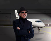 站立在私人喷气式飞机旁边的商人 免版税库存图片