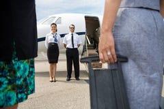 站立在私人喷气式飞机附近的飞行员和空中小姐 免版税库存图片