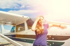 站立在私人飞机附近的年轻愉快的妇女 免版税图库摄影