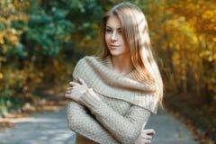 站立在秋天公园的毛线衣的美丽的女孩 免版税库存照片
