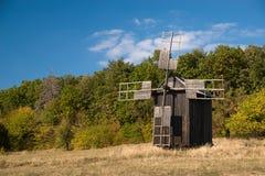 站立在秋天森林边缘的风车 库存图片