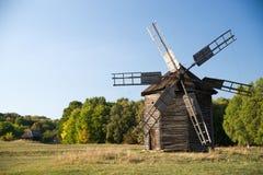 站立在秋天森林边缘的风车 库存照片
