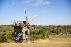 站立在秋天森林边缘的风车 免版税库存照片