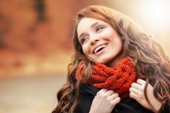 站立在秋天风景的微笑的妇女 免版税库存图片