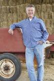 站立在秸杆大包和老农场设备前面的农夫 免版税库存照片