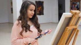 站立在空白的帆布藏品刷子前面的妇女艺术家 股票录像