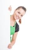 站立在空白的横幅后的可爱的女性雇员 免版税图库摄影
