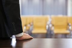 站立在空的会议厅里的商人 库存图片