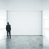 站立在空的办公室的商人 库存图片