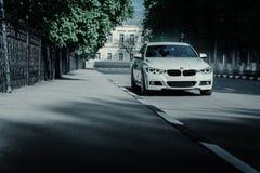 站立在空的柏油路的白色BMW 3系列F30汽车在夏天白天 免版税库存照片