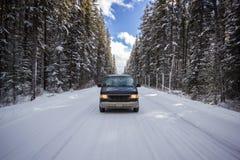 站立在空的路中间的老汽车审阅与白色雪,班夫国家公园加拿大的大森林coverd 库存照片