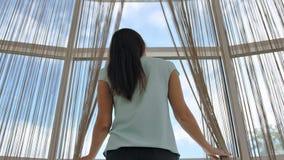 站立在窗口和开幕附近的少妇 股票录像