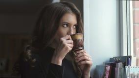 站立在窗口和饮用的coffe旁边的美丽的女孩 影视素材
