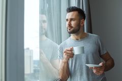 站立在窗口唯一生活方式概念饮用的咖啡想法附近的学士人每日惯例 库存照片