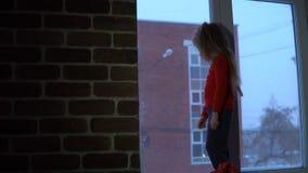 站立在窗口基石的小逗人喜爱的女孩,看在一种多雪的都市风景