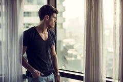 站立在窗口旁边的性感的年轻人 免版税库存照片
