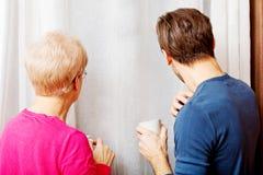 站立在窗口旁边的母亲和儿子,谈话互相和drinikin咖啡或者茶 库存图片