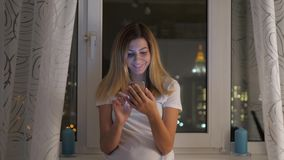 站立在窗口的妇女有夜视图和用途智能手机 股票视频