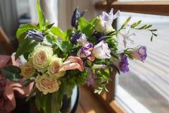 站立在窗口附近的不同的五颜六色的花惊人的花束  库存照片