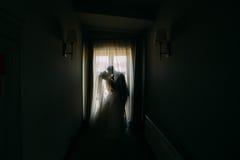 站立在窗口附近的亲吻的新婚佳偶夫妇的剪影在暗室 库存图片