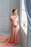 站立在窗口附近的桃红色晚礼服的孕妇 方式射击 免版税库存图片