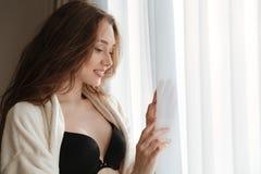 站立在窗口附近的浴巾和女用贴身内衣裤的微笑的妇女 库存图片