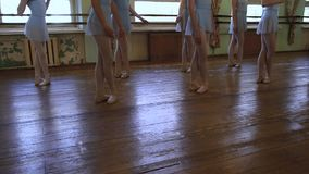 站立在第三个位置的女孩的腿在芭蕾教训期间在磨损的教室 影视素材