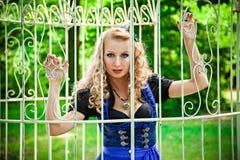 站立在笼子后的浪漫女孩在庭院里 免版税图库摄影