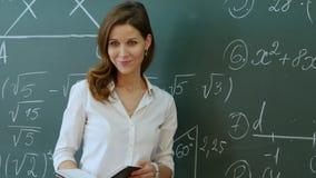 站立在类前面的老师要求问题和微笑 库存图片