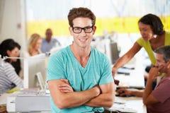 站立在繁忙的创造性的办公室的人画象 免版税库存照片