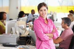 站立在繁忙的创造性的办公室的妇女画象 图库摄影