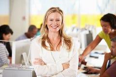 站立在繁忙的创造性的办公室的妇女画象 库存照片