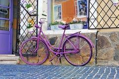 站立在纪念品店前面的紫色自行车 免版税图库摄影