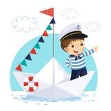 站立在纸小船的水手服装的小男孩 免版税库存照片
