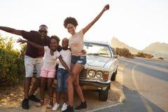 站立在经典汽车旁边的家庭画象 免版税图库摄影