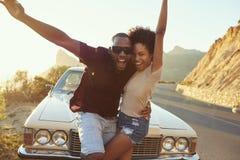 站立在经典汽车旁边的年轻夫妇画象  免版税库存照片