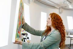 站立在绘画美术画廊前面的年轻白种人妇女  免版税库存照片