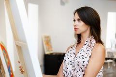 站立在绘画美术画廊前面的年轻白种人妇女  免版税图库摄影
