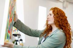 站立在绘画美术画廊前面的年轻白种人妇女  库存照片