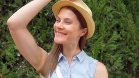 站立在绿色公园的愉快的微笑的少妇画象  在慢动作的风打击女性头发 股票录像