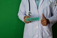 站立在绿色背景的医生 拿着药房纸文本 库存照片