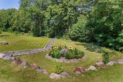 站立在绿色草坪的厚实的灌木附近的一条小长凳有与石头围拢的花的一张美丽的花床的 免版税库存照片